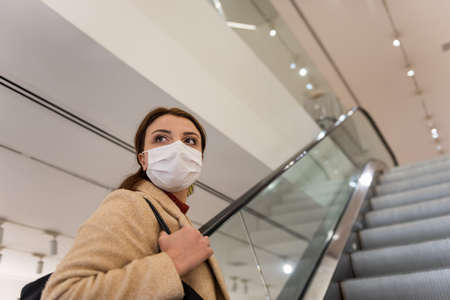 Beautiful girl wearing protective medical mask and fashionable clothes uses escalator in shopping center.New normal lifestyle concept.