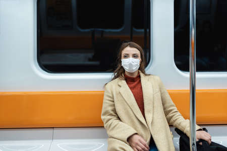 Beautiful woman wearing protective disposable mask keeps social distance by sitting alone while transporting.New normal lifestyle concept. Stock Photo