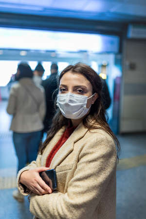 Beautiful woman wearing protective medical mask and fashionable clothes waits in line row.New normal concept.