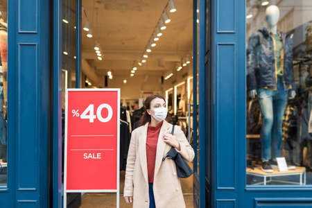 Beautiful girl wearing protective medical mask and fashionable clothes shows sale,discount clothes store. New normal lifestyle concept.