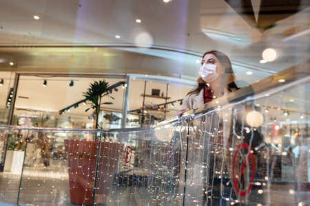 Beautiful girl wearing protective medical mask and fashionable clothes looks at behind of showcase. New normal lifestyle concept.