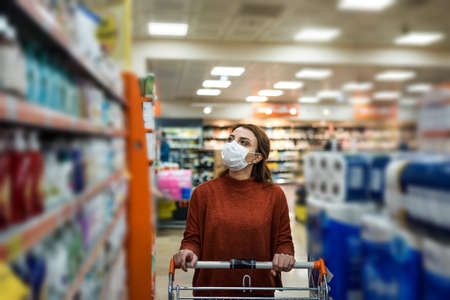 Beautiful woman wearing protective disposable mask shopping in mall. New normal concept during pandemic corona,covid19.