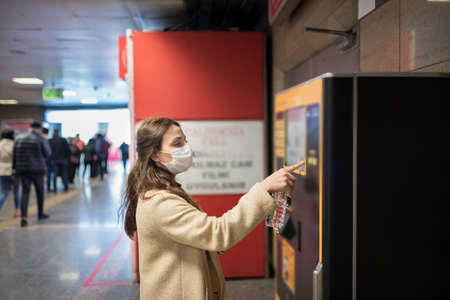 Beautiful girl wearing protective medical mask and fashionable clothes uses ATM machine for money.New normal concept during pandemic corona,covid19. Stock Photo
