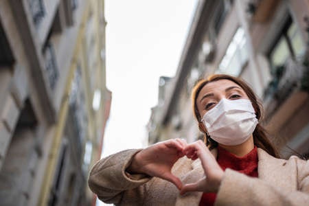 Beautiful girl wearing protective medical mask and fashionable clothes does heart shape at street. New normal lifestyle concept.
