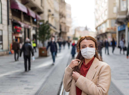 Beautiful girl wearing protective medical mask and fashionable clothes stands at street. New normal lifestyle concept. Stock Photo