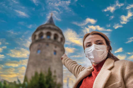 Beautiful girl wearing protective medical mask and fashionable clothes does heart shape with view of Galata Tower landmark.
