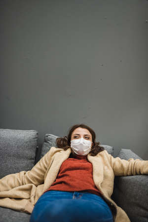Beautiful woman wearing protective medical mask and fashionable clothes rests in chair.New normal concept.