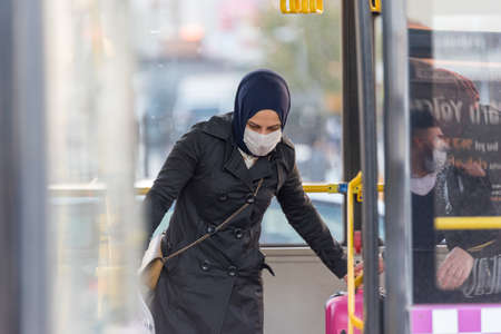 Unidentified Turkish people wearing protective face masks move to get out to buses during coronavirus COVID-19 epidemic.Istanbul,Turkey.16 November 2020