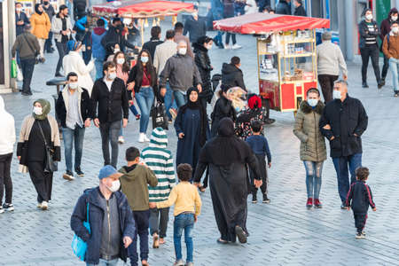 Unidentified Turkish people wearing protective face masks walking closely at the streets without social distance coronavirus COVID-19 epidemic.Istanbul,Turkey.16 November 2020