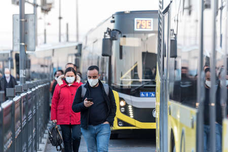 Unidentified Turkish people wearing protective face masks in lines move to get in or out to buses during coronavirus COVID-19 epidemic.Istanbul,Turkey.16 November 2020 Editorial
