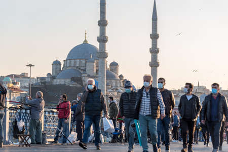 Unidentified Turkish people wearing protective face masks walking at Galata bridge during coronavirus COVID-19 epidemic.Istanbul,Turkey.16 November 2020