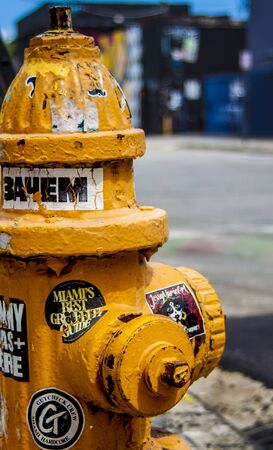 Miami Florida  - August 29, 2018 Wynwood Miami Art Area Corner Yellow Fire Hydrant Covered in Stickers and Graffiti.