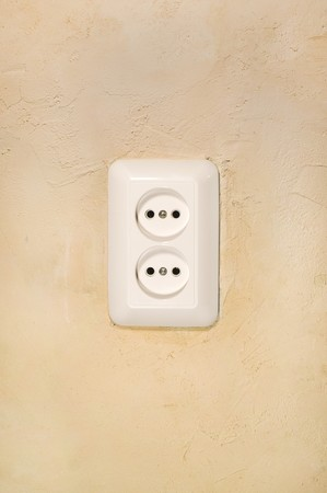 euro screw: White electric outlet on gravel plaster as a background.