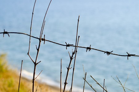 seacoast: Barbed wire on seacoast. Stock Photo