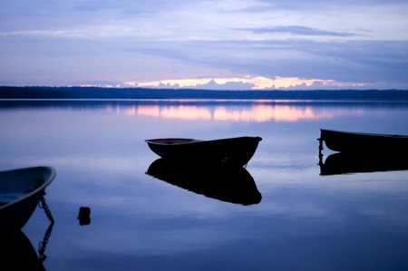 Blue quiet. Moored boat with reflection on the calm water of the lake. Stock Photo - 4351381