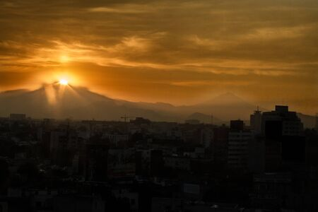 view of the Iztaccíhuatl volcano mountain rais above Mexico city.The city surrounded by mountains and volcanoes that reach elevations of over 5,000 meters
