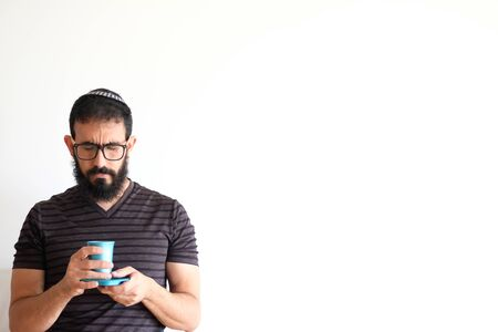 Bearded Jewish  holding a cup of wine for the Kidush on Shabbat. The man is standing in front of a white background with a serious expression