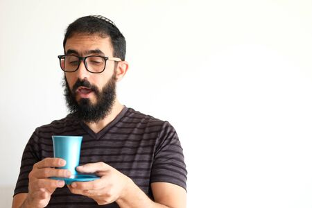 Bearded Jewish  holding a cup of wine for the Kidush on Shabbat. The man is standing in front of a white background and pronouncing the blessing Stock fotó