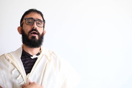 Bearded Jewish with a  Tallit (talis) and Praying. The man is standing in front of a white background. the man is singing a pray