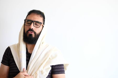 Bearded Jewish with a  Tallit (talis) . The man is standing in front of a white background and he is in the middle of a pray with he's eyes close and concentrate. Stock Photo