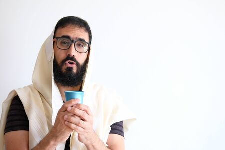 Bearded Jewish with a  Tallit (talis) and holding a cup of wine for the Kidush. The man is standing in front of a white background and has the Tallit covering his head Stock Photo