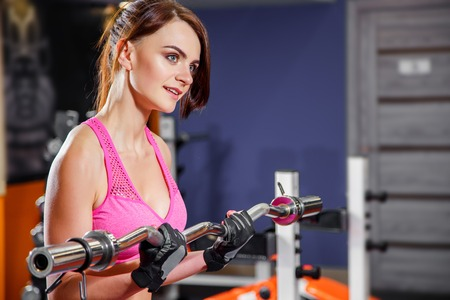 Young fitness woman doing exercise with barbell in the gym.