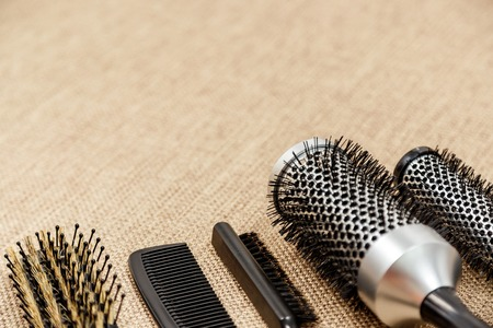 salon background: Combs and hairdresser tools on beige background