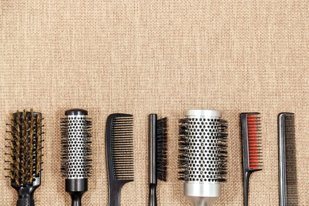 salon background: Hairdressing tools on beige background with space at top