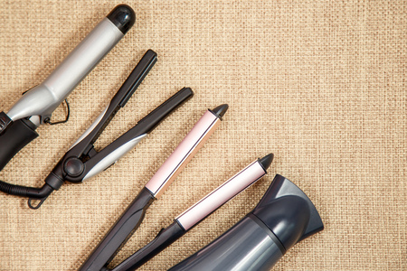 salon background: Collection of the professional hairdresser appliances - hair dryer, curling, corrugation, straightener top view