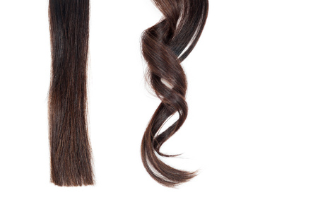 salon background: A strand of straight hair and curl on white isolate. Stock Photo