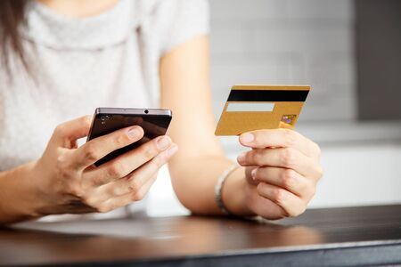 Online payment, women's hands holding a credit card and using smart phone for online shopping