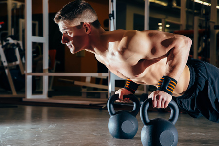 Strong handsome man doing push-ups on dumbbells in a gym as bodybuilding exercise, training his muscles 版權商用圖片