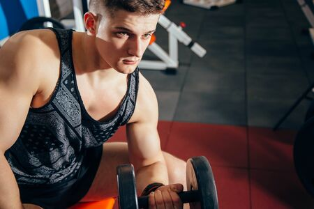 Sport, bodybuilding, training and people concept - close up of young man with dumbbell flexing muscles in the gym