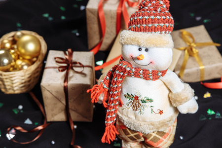 Cheerful snowman in red cap and scarf over blurred christmas gifts boxs Stock Photo