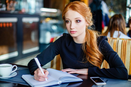 Young creative female writer pondering over conclusion of essay to give the reader something to think about inspiring by warm atmosphere in comfortable coffee shop writing down script into notebook