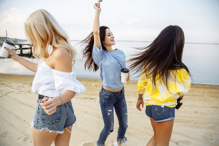 Vacation. Beach Party. Group of happy young women dancing at the beach on summer sunset.