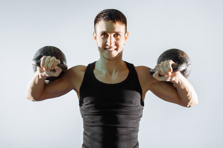 Portrait of a smiling muscular man performing exercises with weights. Stock Photo