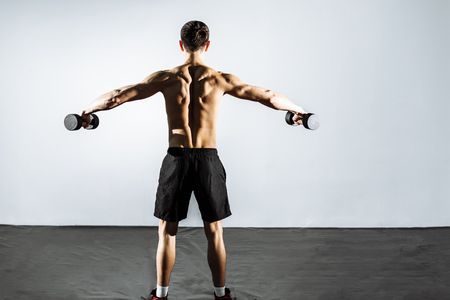 The view from the back. Muscular man doing exercises with dumbbells.