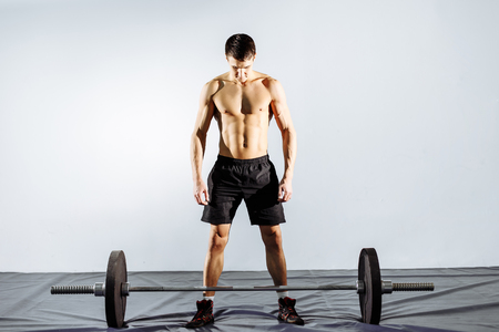 Muscular man working out in gym doing exercises with barbell, strong male naked torso abs. Stock Photo