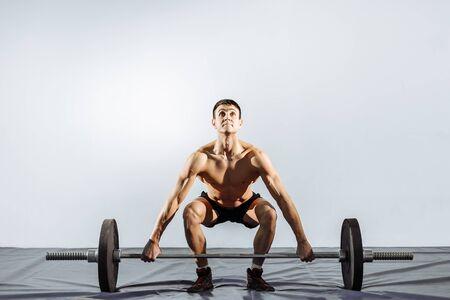Hübscher junger Mann, der Übungen in der Turnhalle tut. Das Konzept von Fitness, Sport und einem gesunden Lebensstil.