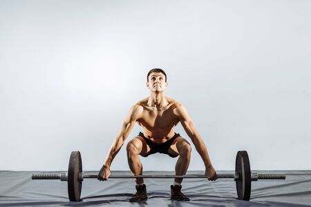 Handsome young man doing exercises in the gym. The concept of fitness, sports and a healthy lifestyle.
