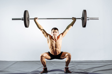 Muscular man workout with barbell at gym. Brutal bodybuilder athletic man with perfect abs, shoulders, biceps, triceps and chest. Standard-Bild