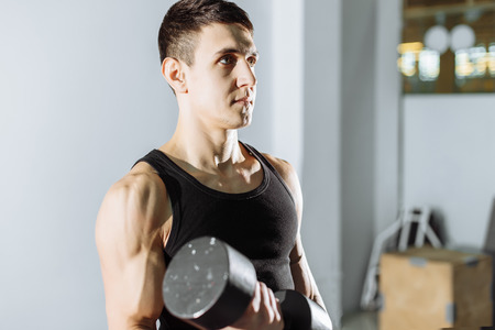 Closeup of a muscular young man lifting weights in the gym.