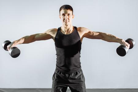 Junger starker Mann, der mit Dummköpfen in der Turnhalle trainiert Standard-Bild