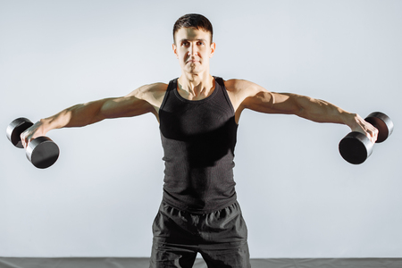 Young strong man exercising with dumbbells in gym Stock Photo