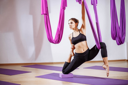 portrait young women making antigravity yoga exercises. Aerial aero fly fitness trainer workout. meditates. harmony and serenity concept Stock fotó - 89944192