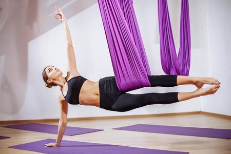 gravedad: Young beautiful yogi woman doing aerial yoga practice in purple hammock in fitness club.