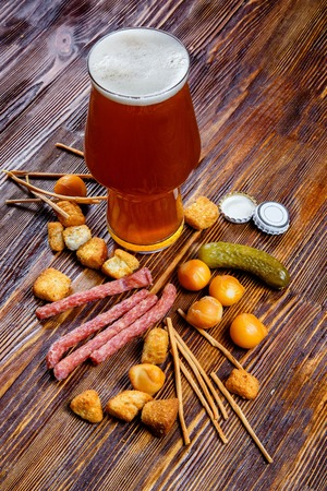 A glass of beer and snacks on a wooden table