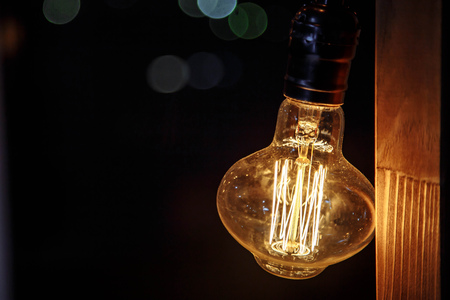 Close up decorative vintage edison style light bulbs against dark background at night.