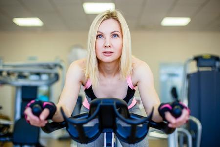 Happy blonde doing indoor biking in a fitness club Archivio Fotografico